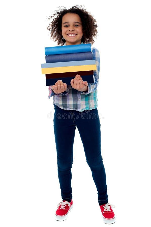 Pile de transport mignonne de petite fille de livres photos stock