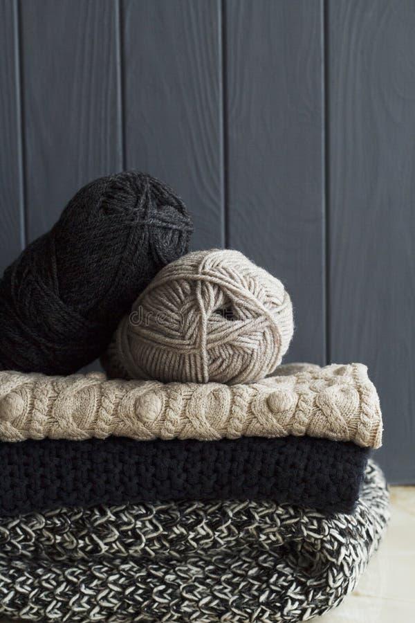 Pile de vêtements chauds des tricots tricotés au-dessus du CCB en bois gris image libre de droits