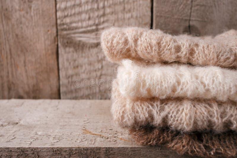 Pile de vêtements des tricots tricotés sur un fond en bois, l'espace de copie Concept simple d'hiver de chute d'automne photo stock