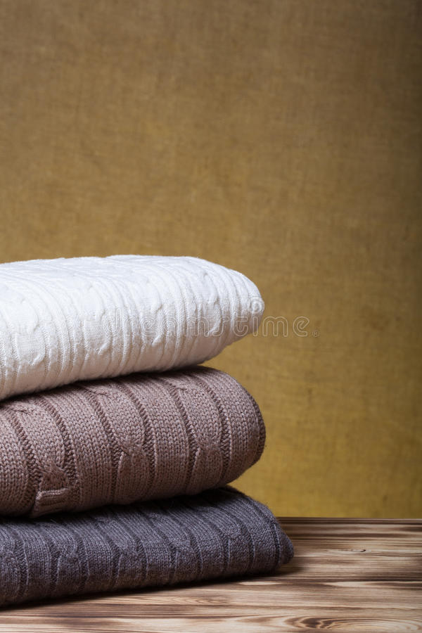 Pile de vêtements tricotés sur la table en bois vis-à-vis d'un Bu defocused images libres de droits