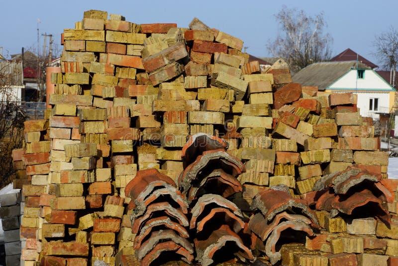 Pile de vieilles briques et tuiles de toit brunes sur une rue rurale images stock