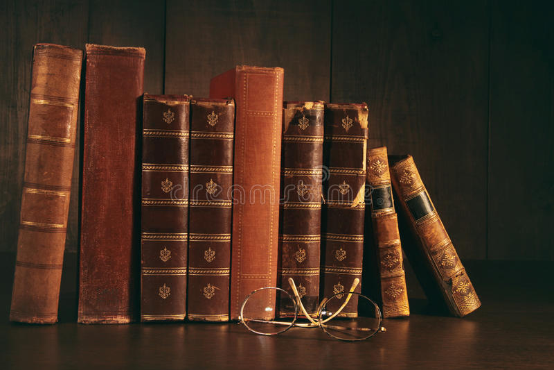 Pile de vieux livres avec des verres sur le bureau image stock