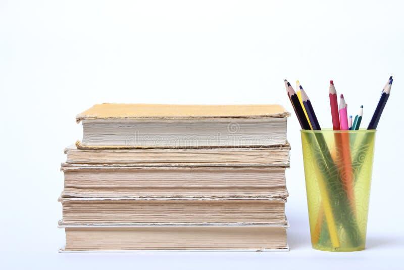 Pile de vieux livres Crayons dans un verre photos stock