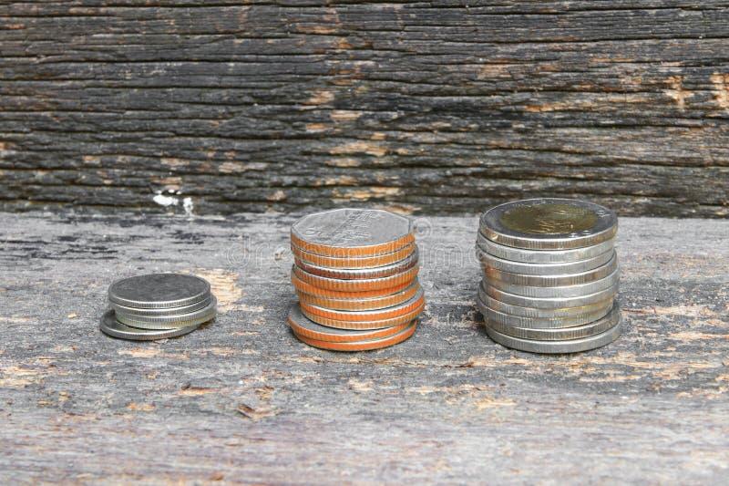 Pile dei soldi della moneta sul fondo di legno del pavimento immagine stock libera da diritti