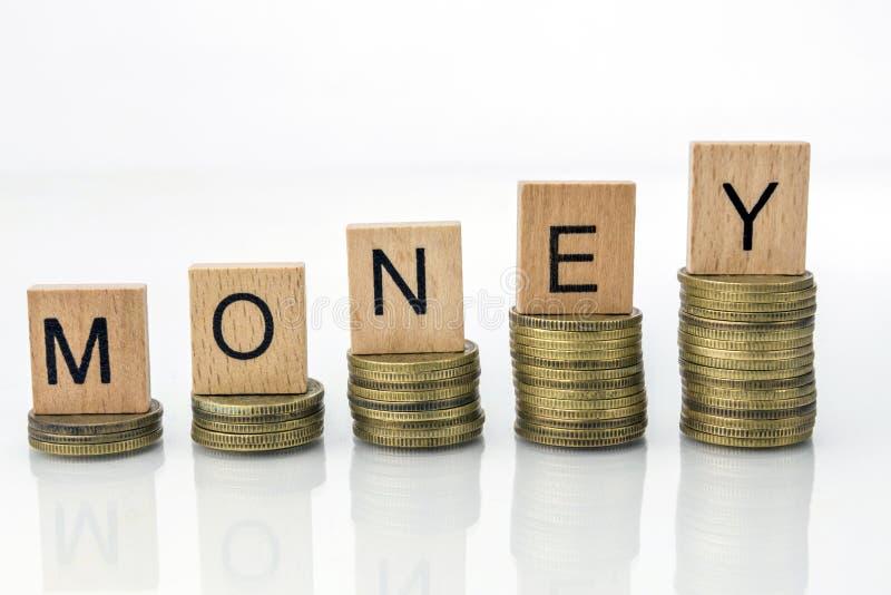 Pile della moneta con i dadi della lettera - soldi fotografia stock libera da diritti