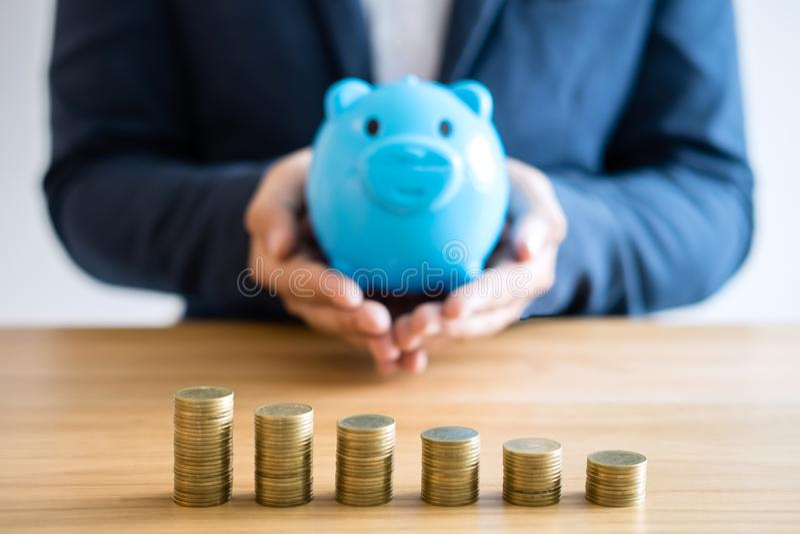 Pile della moneta per aumentare affare crescente al profitto e risparmio con il porcellino salvadanaio, i soldi di risparmio per  fotografia stock