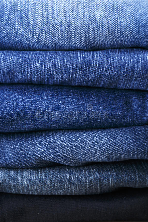 Pile of denim pants. Stack of blue jeans pants on a wooden table royalty free stock photo