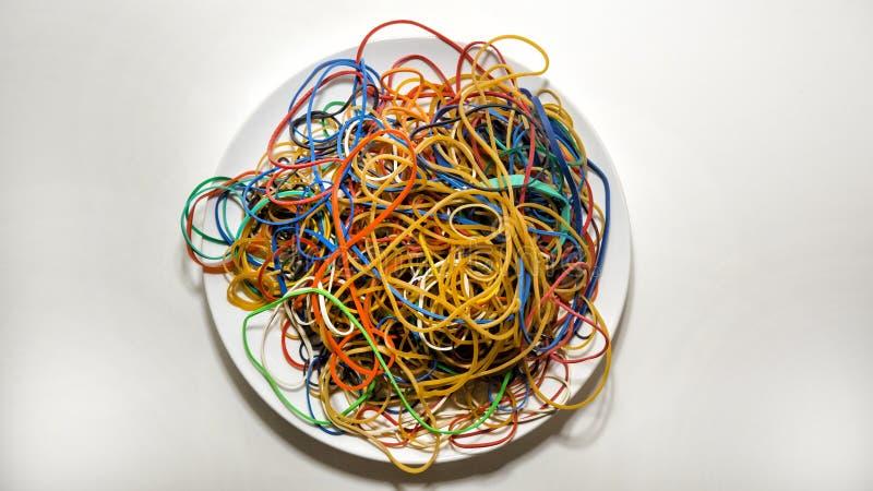 Pile des bandes élastiques d'un plat blanc image libre de droits