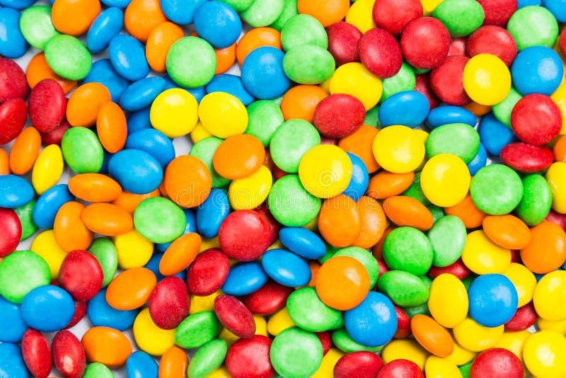 Pile des bonbons au chocolat délicieux colorés à lait dans la coquille croquante photos stock