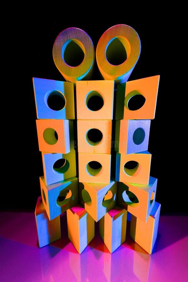 Pile des briques de jouet dans la lumière colorée photographie stock libre de droits