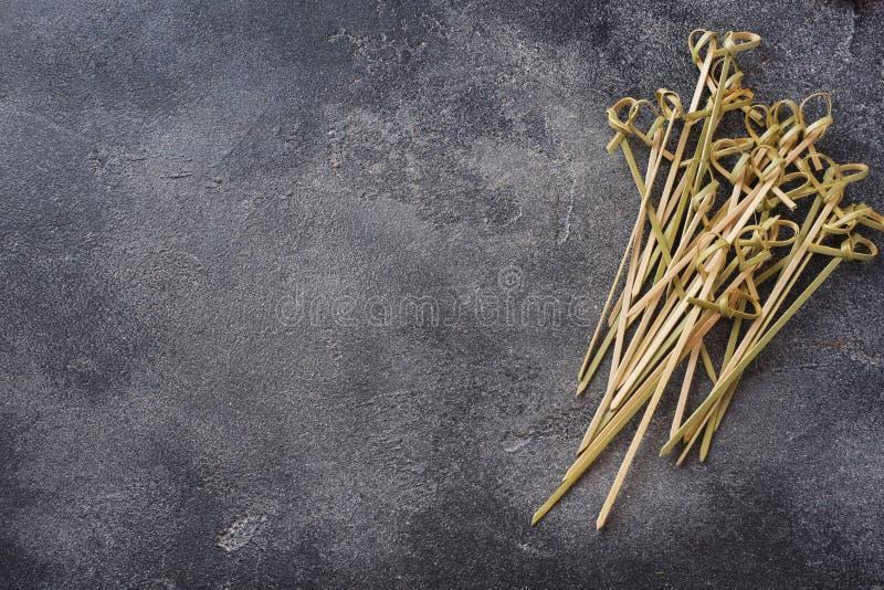 Pile des brochettes en bambou sur le fond concret foncé avec l'espace de copie photo stock