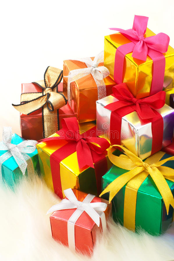 Pile des cadeaux sur la fourrure fausse blanche. (verticale) photographie stock libre de droits