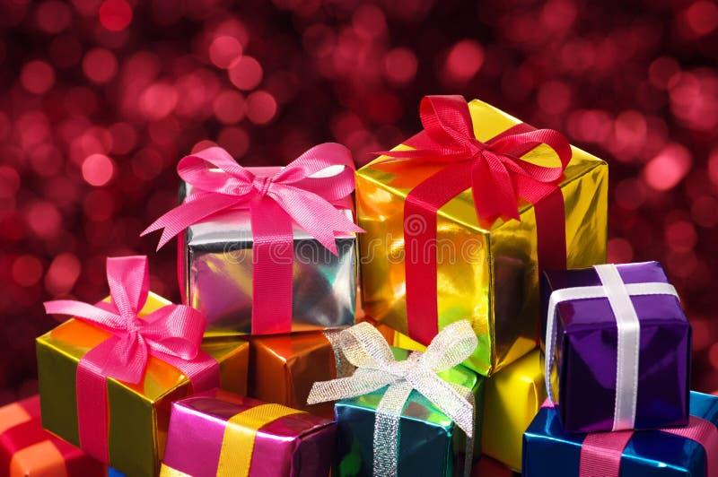 Pile des cadeaux sur le fond trouble rouge de lumières. images libres de droits