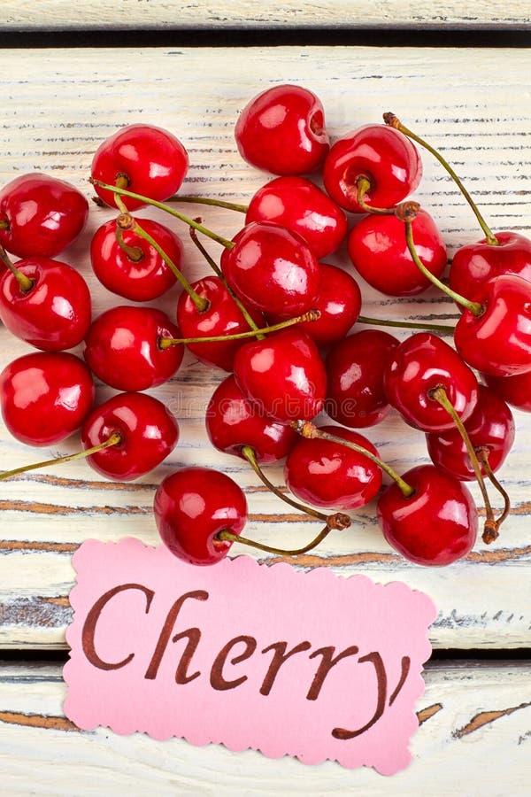 Pile des cerises et de la carte de papier rouges photo stock