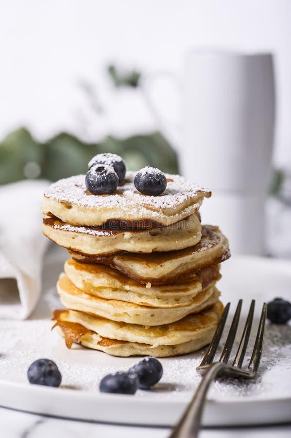 Pile des crêpes américaines avec les myrtilles et le sucre en poudre photos stock