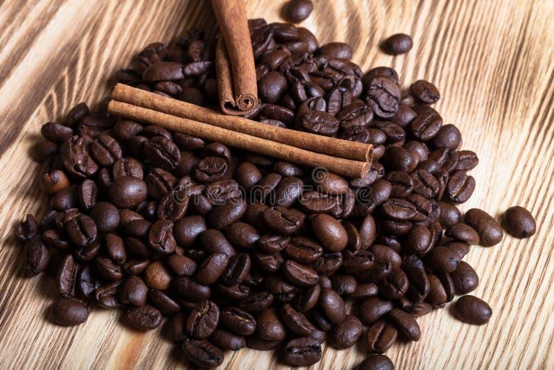 Pile des grains de café avec de la cannelle sur la table en bois pour le backgroun photographie stock libre de droits
