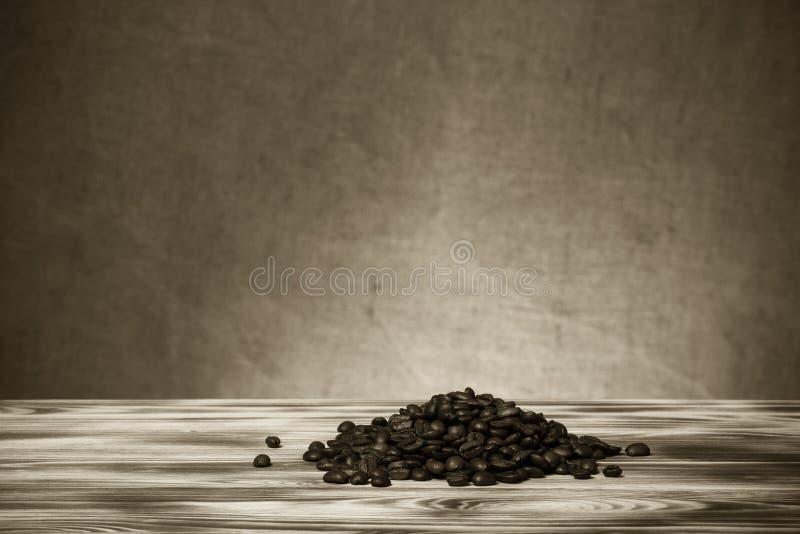 Pile des grains de café sur la table en bois vis-à-vis d'une toile de jute defocused photos stock