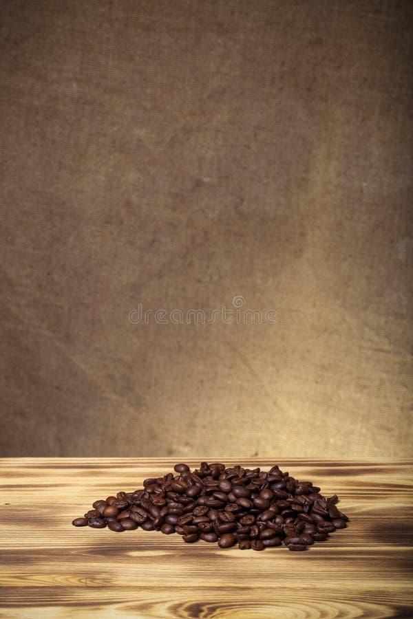 Pile des grains de café sur la table en bois vis-à-vis d'une toile de jute defocused image stock