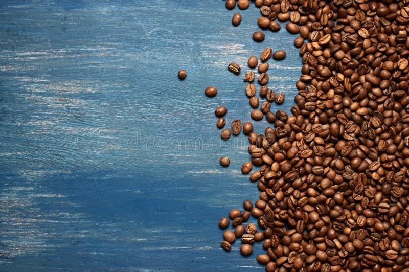 Pile des grains de café sur le bois bleu photo stock