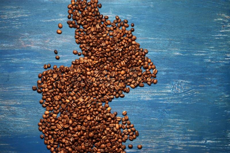 Pile des grains de café sur le bois bleu photographie stock libre de droits