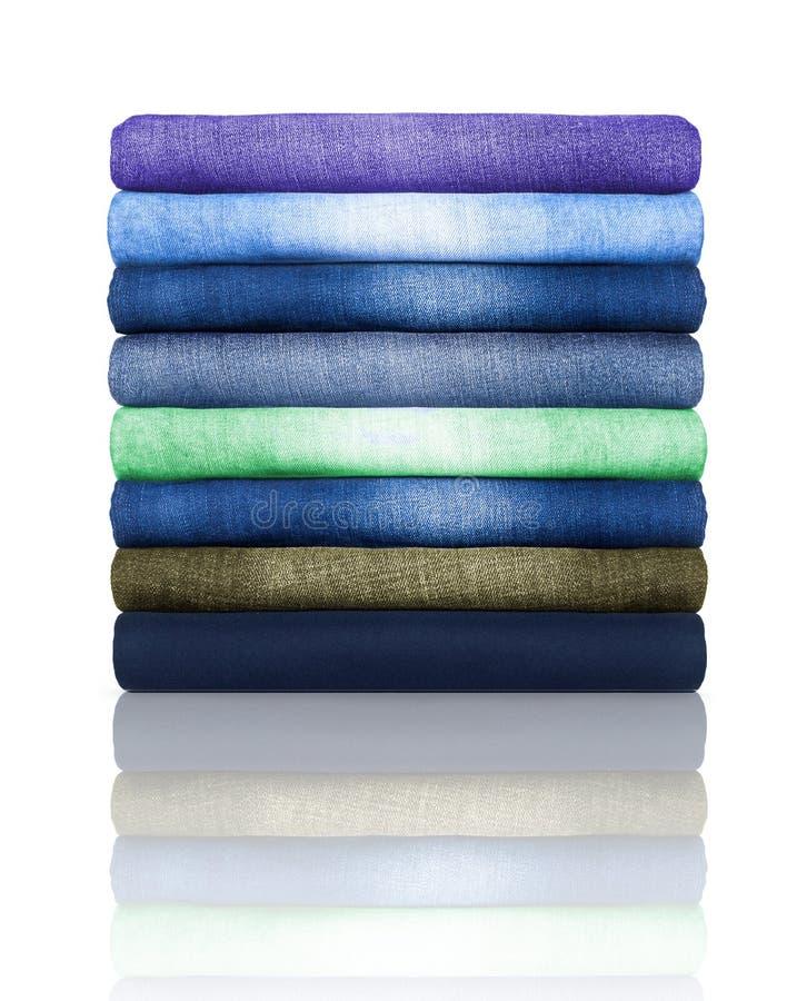 Pile des jeans colorés d'isolement sur un fond blanc image libre de droits