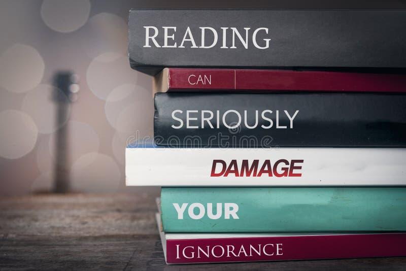 Pile des livres avec dire des textes : La lecture peut endommager votre ignorance photos stock