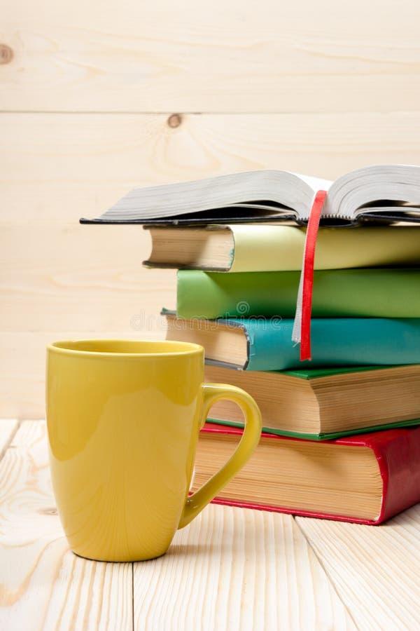 Pile des livres colorés, du livre ouvert et de la tasse sur la table en bois image libre de droits