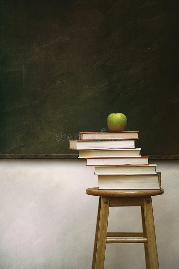 Pile des livres et de la pomme sur des selles image libre de droits