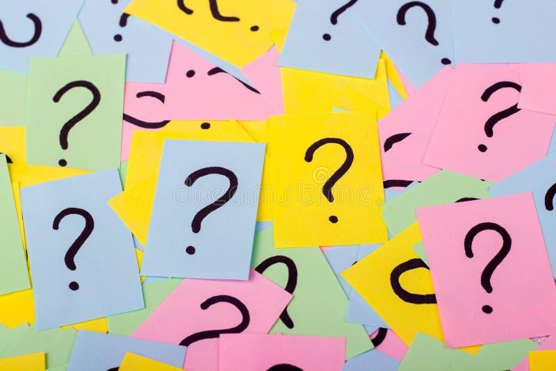 Pile des notes de papier colorées avec des points d'interrogation closeup images stock