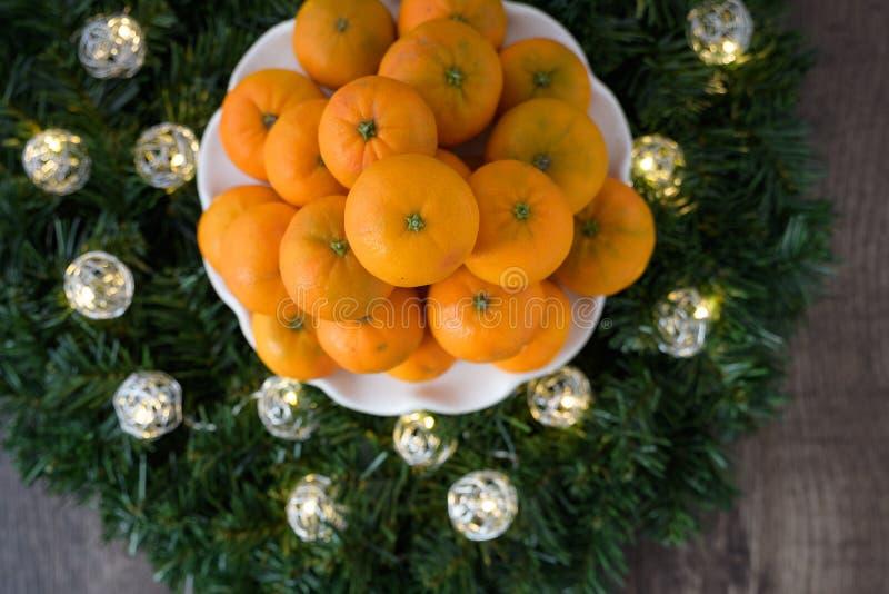 Pile des oranges de satsuma d'un plat blanc, dans une guirlande avec des lumières de Noël de LED sur un fond en bois images stock