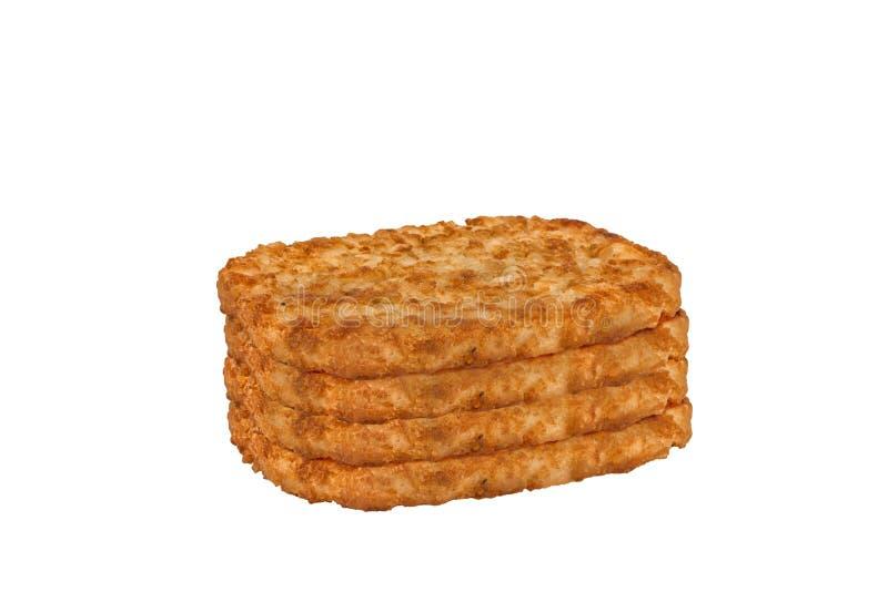 Pile des petits pâtés de pommes de terre rissolées pour le petit déjeuner, d'isolement images stock