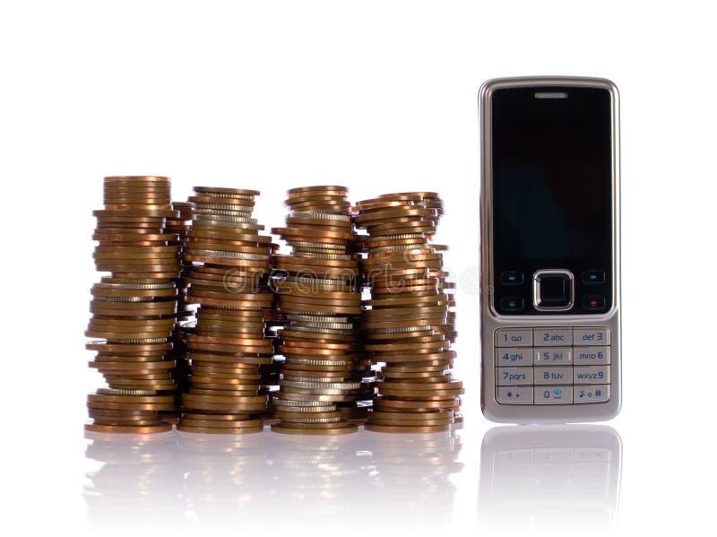 Pile des pièces de monnaie BRITANNIQUES contre le téléphone portable photos libres de droits