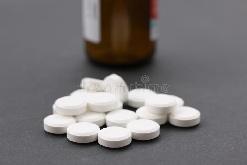 Pile des pilules blanches avec la bouteille de pilule brune dans la bouteille de backgroundll illustrant des vitamines ou la dépe images libres de droits
