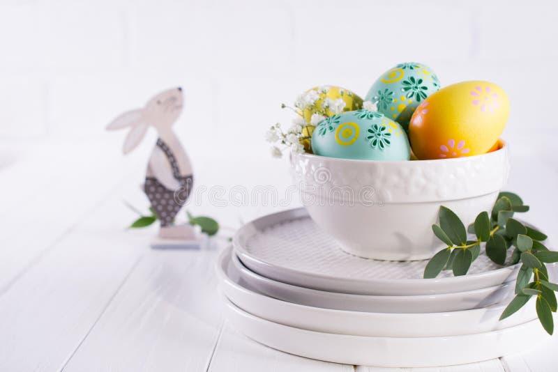 Pile des plats et de la cuvette avec les oeufs de pâques colorés, ressort Décoration de Pâques sur le blanc photographie stock libre de droits