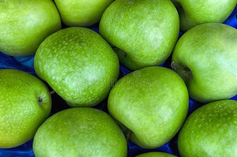 Pile des pommes vertes mûres fraîches à un marché local photographie stock