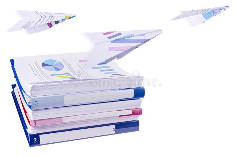 Pile des reliures à anneaux de bureau avec les avions de papier volants image libre de droits