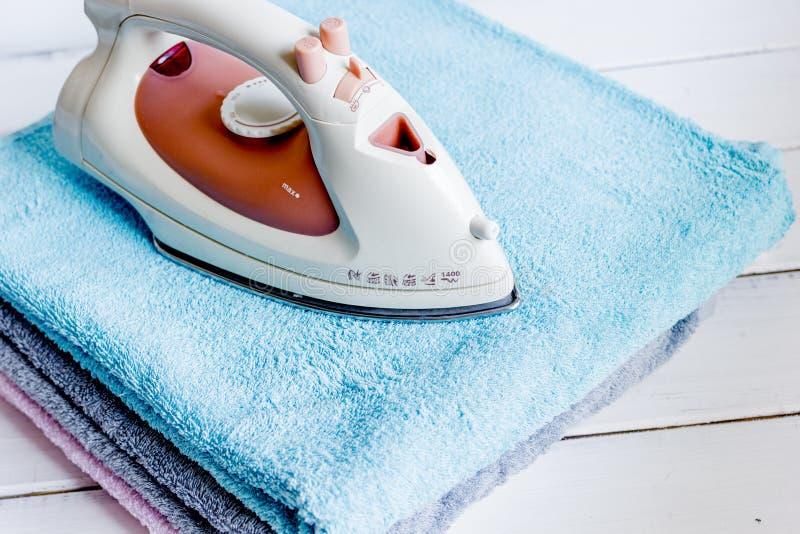 Pile des serviettes colorées avec du fer à l'arrière-plan en bois de blanchisserie photographie stock libre de droits