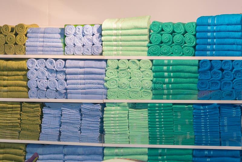 Pile des serviettes multicolores sur l'étagère photos stock
