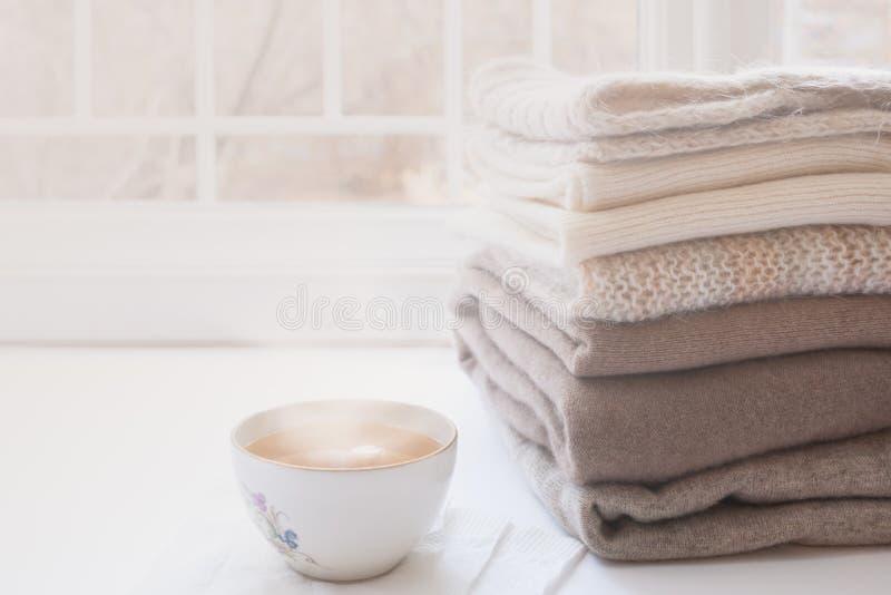 Pile des tricots et de la tasse chauds de thé chaud sur le rebord de fenêtre sur le fond blanc de fenêtre image stock