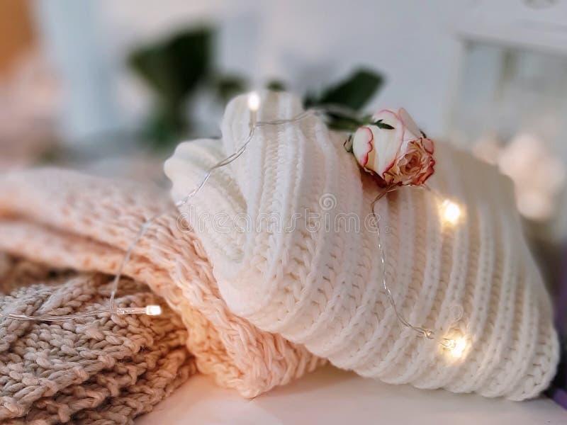 Pile des vêtements tricotés d'hiver avec la rose et les lumières sur le fond brouillé photographie stock