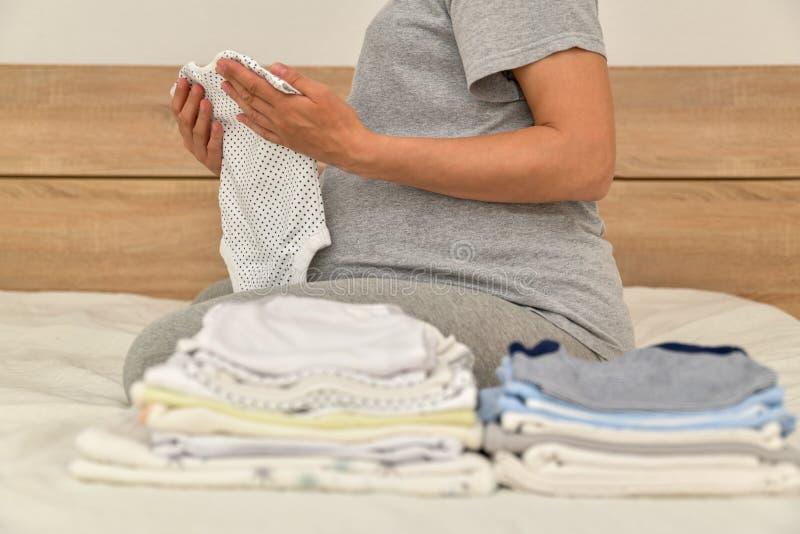Pile des v?tements de b?b? et de la femme enceinte sur un lit photographie stock