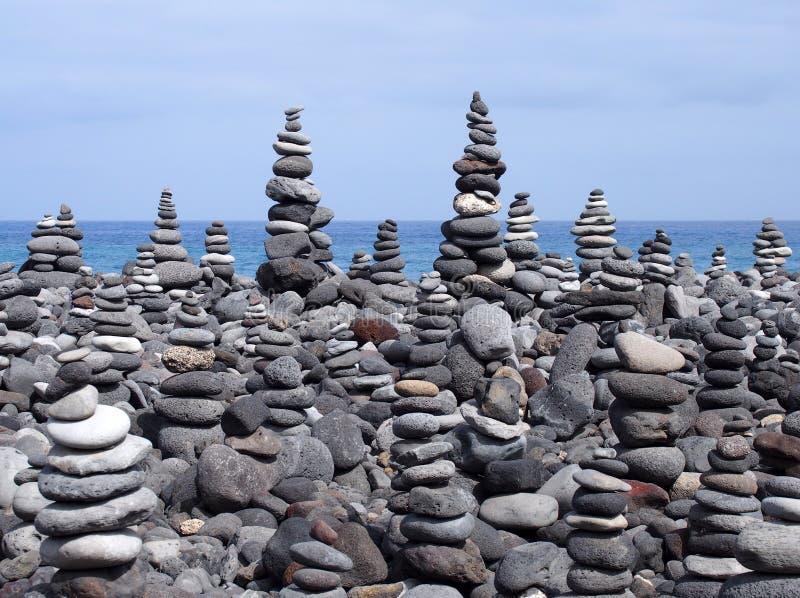 Pile di arte della roccia e torri di pietre e di ciottoli grigi su una spiaggia immagine stock libera da diritti