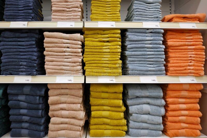 Pile di asciugamani variopinti impilati sopra a vicenda sugli scaffali di negozio fotografie stock libere da diritti