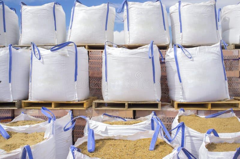Pile di grandi sacchi della sabbia della rafia impilati sopra i wi di legno dei pallet fotografia stock