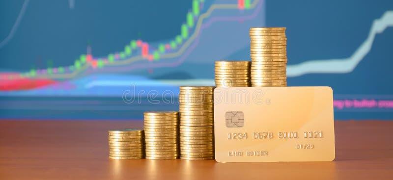 Pile di monete e di carta di credito dorate sui precedenti del grafico di crescita su esposizione fotografia stock