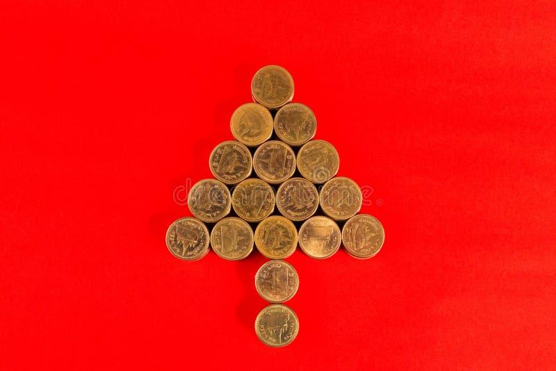 Pile di monete sistemate come forma dell'albero di Natale o della freccia sulla r immagini stock libere da diritti