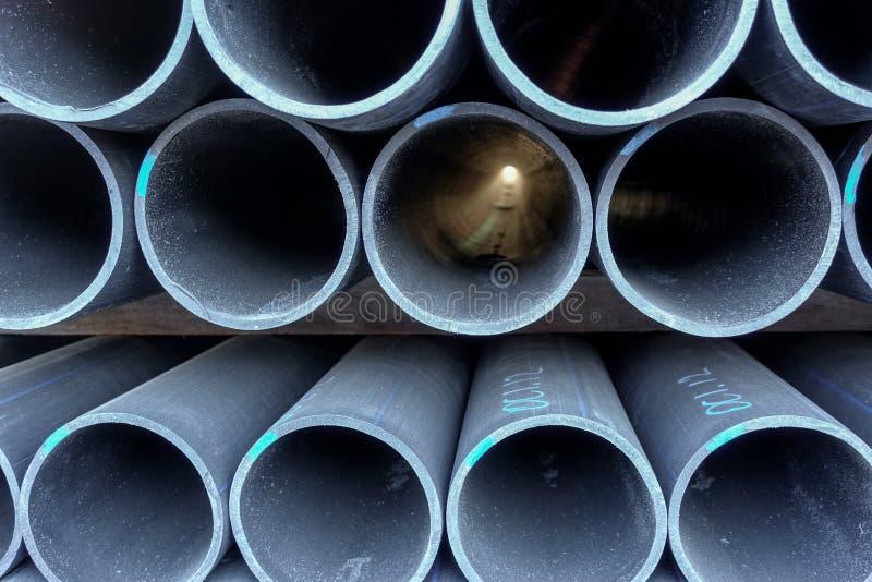 Pile di tubi di plastica neri L'estremità rotonda si chiude su fotografia stock