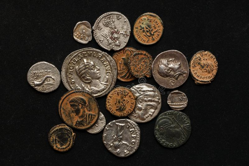 Pile of different ancient coins on black background.  stock photo
