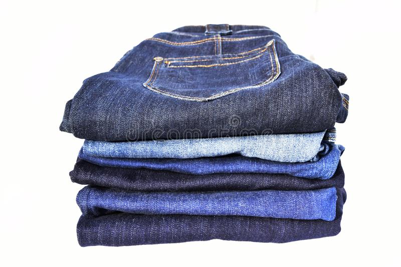 Pile of blue jeans on white background stock photos
