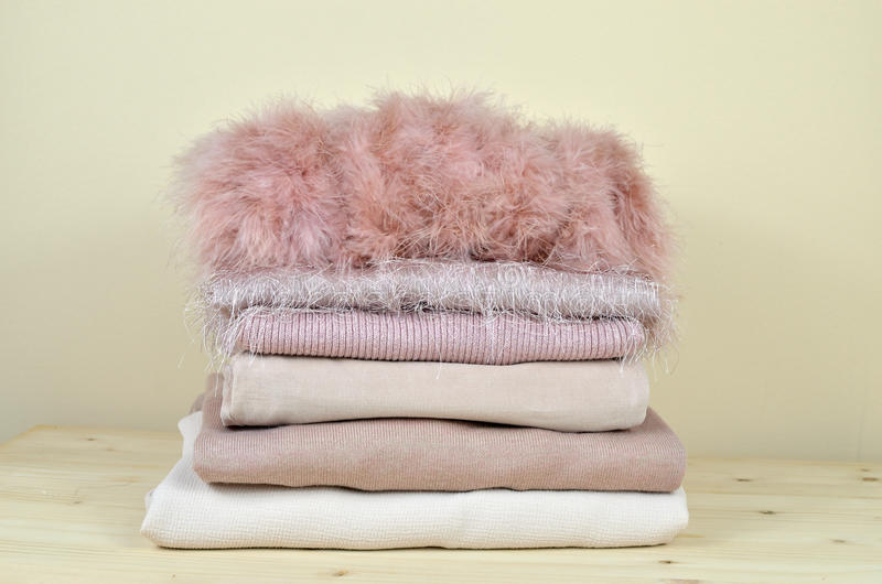 Pile of Different Pink Garments. Pile of pink garments of different materials - feather, cotton, woolen, corduroy velvet - on wooden shelf stock photo